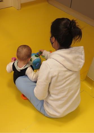 Une puericultrice joue avec un bébé
